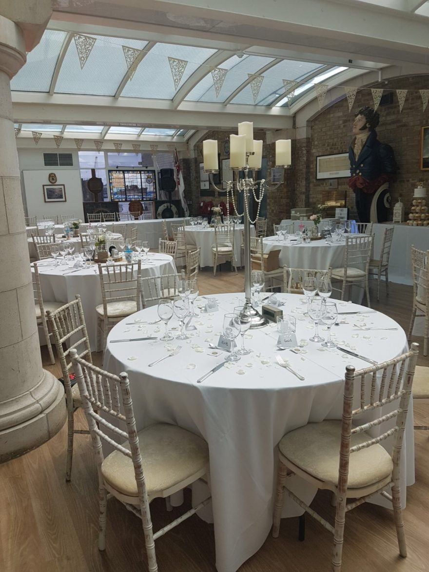 Round tables wedding set up in the Drill Deck of our Tower Hill Venue, HMS President, Royal Navy London venue